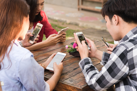 CHIANG MAI, THAILAND - FEBRUARY 21st, 2018: Hands of five teenagers use Apple smartphone together on table Editorial