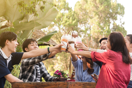 Group of 6 teenagers having fun together without liquor in cafe in afternoon drink milk tea, pink milk and chocolate in plastic glass Standard-Bild