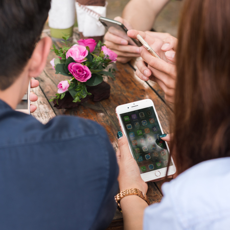 CHIANG MAI, THAILAND - FEBRUARY 21st, 2018: Hands of four teenagers use Apple smartphone together on table