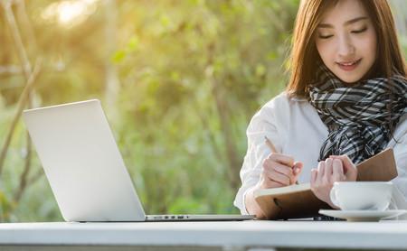 Hermosa joven adolescente freelance trabajo con laptop escribir nota con una taza de café con leche en la luz del sol, estilo de vida independiente conceptual