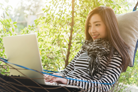 Young woman with scarf use laptop lying in hammock, freelance life style conceptual, work anywhere