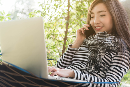 Young woman with scarf use laptop lying in hammock while talk via cell phone, freelance life style conceptual, work anywhere Stock Photo