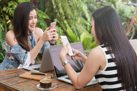 Two Beautiful freelance woman work with laptop and smartphone in coffee shop, modern generation lifestyle