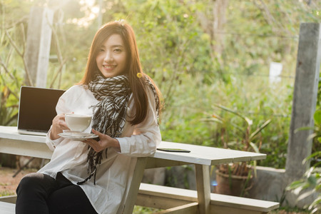 Beautiful young teenage woman freelance work with laptop write down note with a cup of latte on sun light, freelance lifestyle conceptual