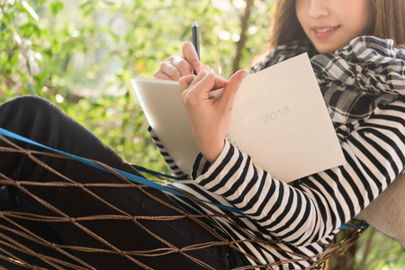 Beautiful young teenage woman write note  in white notebook Stock Photo