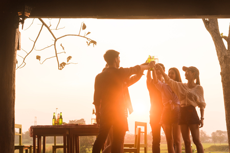 Group of 6 teenager have dinner party celebrating at sunset with beautiful landscape background Imagens