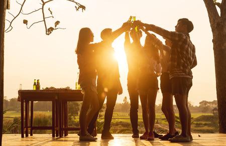 Eine Gruppe von 6 Teenagern hat eine Dinnerparty, die bei Sonnenuntergang feiert und auf Erfolg anstößt