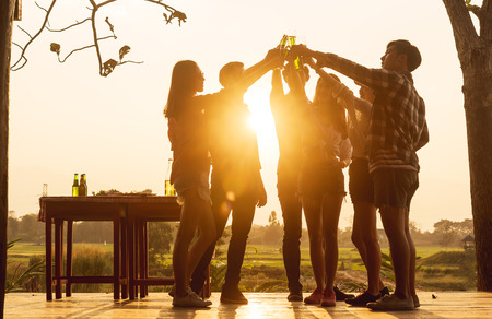 Group of 6 teenager have dinner party celebrating at sunset toasting for success