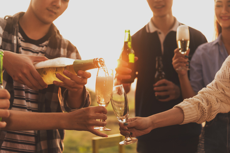 Group of 6 teenager have dinner party celebrating at sunset pouring champange in to glasses Stok Fotoğraf