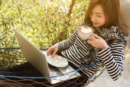 Young woman having coffee in hammock while use laptop, freelance life style conceptual, work anywhere
