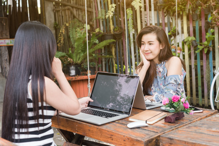 Two teenage women meet in coffee shop use laptop together in afternoon, life style of new teenager with blank screen on laptop