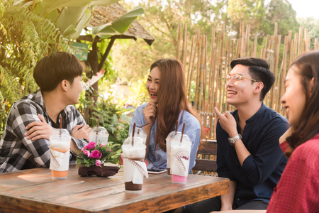 Group of 6 teenagers having fun together without liquor in cafe in afternoon drink milk tea, pink milk and chocolate in plastic glass 写真素材