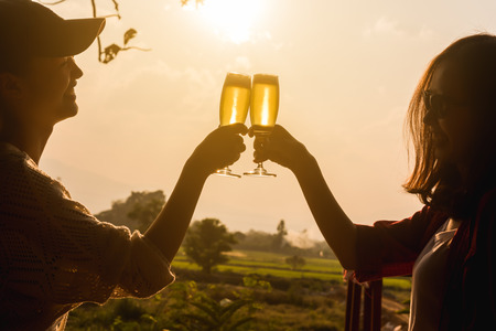 Hands of two women toast champange celebrating under afternoon sunlight, celebrating occation 스톡 콘텐츠