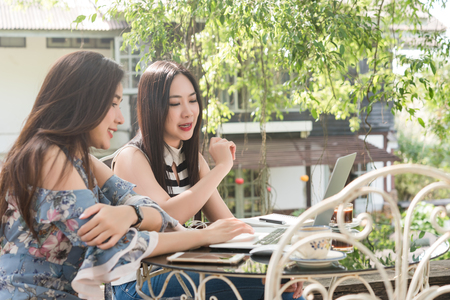 Two teenage women meet in coffee shop use laptop together in afternoon, life style of new teenager Stok Fotoğraf