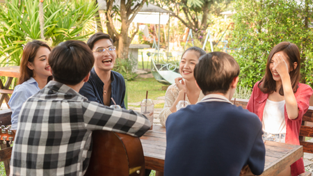 Group of friends hang out in cafe play guitar and sing also use smartphone play social media 스톡 콘텐츠