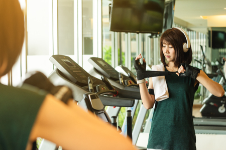 Beautiful asian woman wearing glove prepare for exercise with on-ear head phone