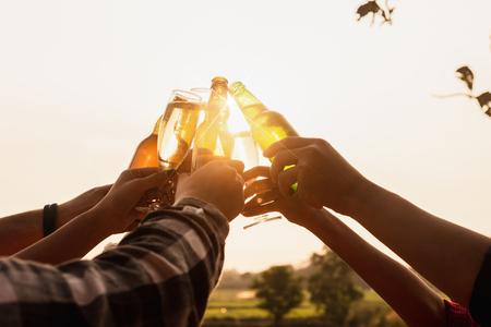 Seis jóvenes empresarios reuniendo brindis por el éxito en la puesta en marcha de negocios, fiesta grupal al anochecer