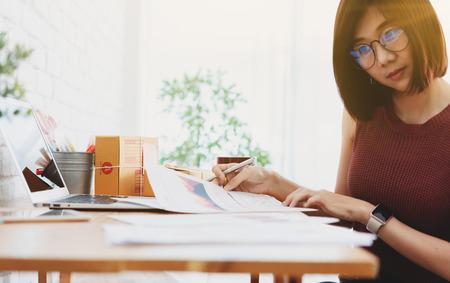 Mujer propietaria de una pequeña empresa, puesta en marcha de un negocio conceptual, trabajo joven empresario con informe en papel