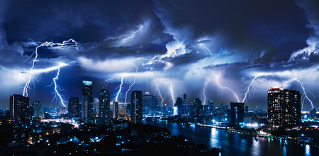 Lightning storm over city in blue light Stock Photo