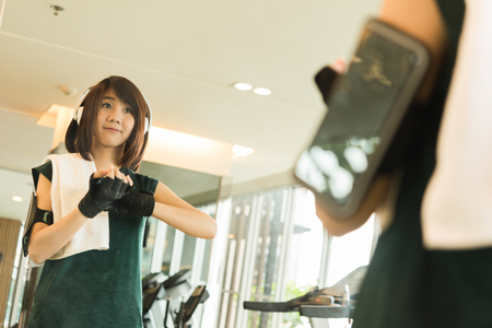 Beautiful young woman prepare for exercise wearing gloves in gym