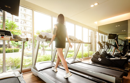 Woman run on running machine with on-ear headphone in gym Stock Photo