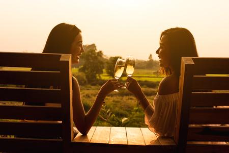 Twee mooie Aziatische vrouwen gooien witte wijn van champange met warm zonsonderganglicht binnen