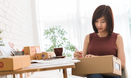 Woman small business owner, business start up conceptual, young entrepreneur preparing parcel for delivery