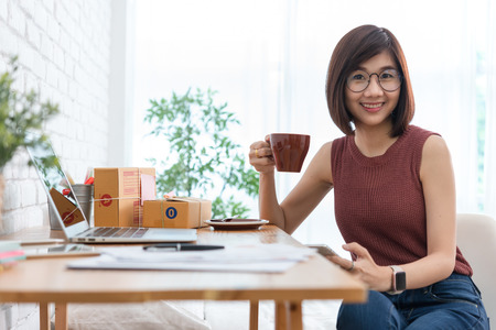 Woman small business owner, business start up conceptual, young entrepreneur use internet with smartphone during morning coffee Stok Fotoğraf - 107592553