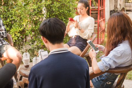 Group of six teenagers play social media in afternoon