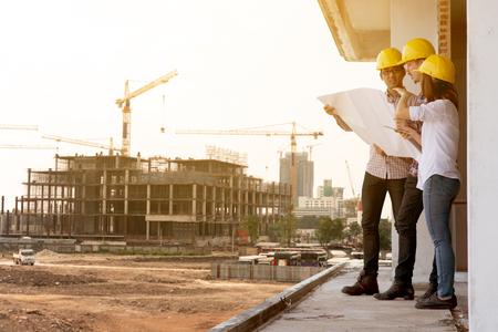 Tres ingenieros de construcción trabajando juntos en la planificación del sitio de construcción para la renovación.