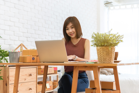 Woman small business owner, business start up conceptual, young entrepreneur check on laptop in the morning with coffee cup Stok Fotoğraf