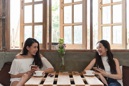 Two teenage women meet in coffee shop use smartphone play social media together in afternoon, life style of new teenager Archivio Fotografico