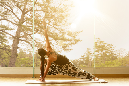 A yoga master practicing yoga performing Trikonasana or triangle pose