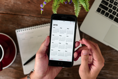 SEPTEMBER 17, 2018: Hands of man use Iphone 8 plus with calendar application on year 2019 Stock Photo - 113347749
