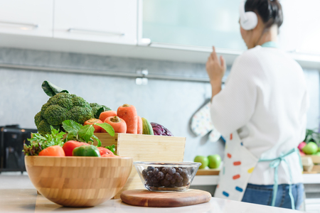 Woman in kitchen with various kind of vegetable and fruits that all are good for health and no meat, vegan lifestyle - Image