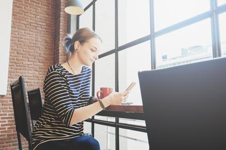 Woman freelance in coffee shop use smartphone Stock Photo - 117635498