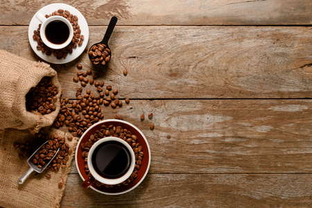Draufsicht auf eine Tasse Americano mit Kaffeebohnenbeutel, Zucker und Zimt auf Holzboden Standard-Bild