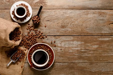 Vista dall'alto di una tazza di americano con un sacchetto di chicchi di caffè, zucchero e cannella su fondo in legno Archivio Fotografico