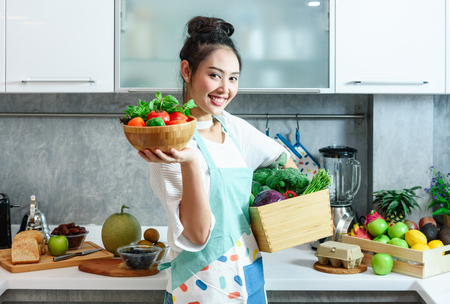 Woman in kitchen with various kind of vegetable and fruits that all are good for health and no meat, vegan lifestyle Stockfoto - 117629911