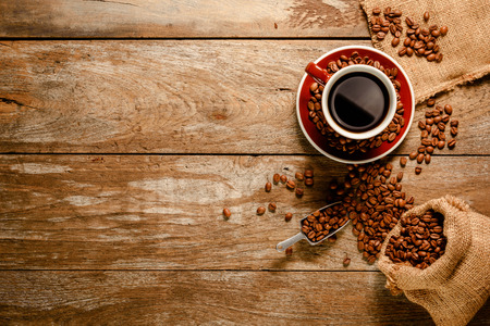 Top view ofa cup of black coffee with coffee bean bag, sugar, cinnamon and grounded coffee on wood background floor