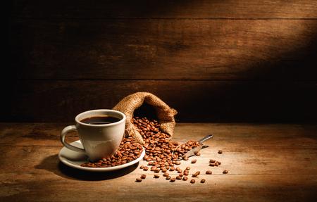 Una taza de café negro o americano con grano de café tostado en bolsa, un buen café para la salud es café negro sin azúcar ni leche.