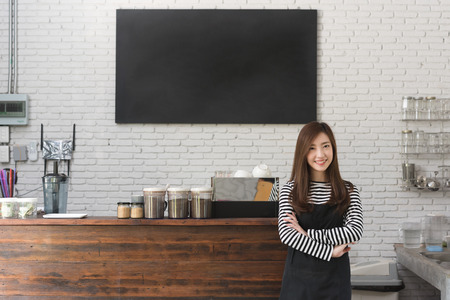 Young woman owner of a cafe stand in front of coffee counter, young entrepreneur conceptual, blank black board on wall