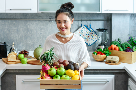 Woman in kitchen with holding a box of various kind of fruits and vegetables that all are good for health and no meat, vegan lifestyle 스톡 콘텐츠
