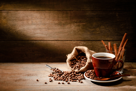 A Cup of black coffee with coffee bean bag and cinnamon on wooden floor with copyspace in background