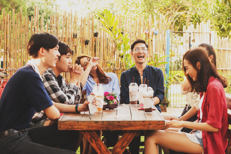 Group of six teenagers having fun together in coffee shop on the afternoon