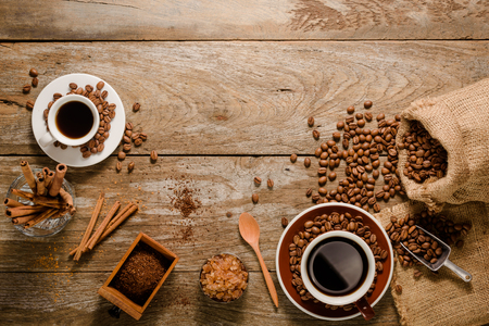 Top view of a cup of americano with coffee bean bag, sugar and cinnamon on wood background floor