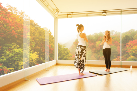 Two women training yoga together in gym face to each other with autumn background red leaf in japan Stock Photo