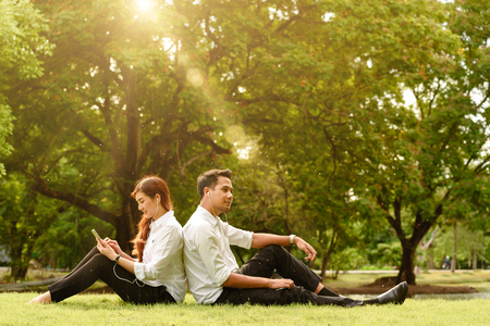 Man and woman in white shirt use smartphone without talk to each other in outdoors park Foto de archivo