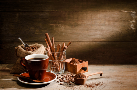 A Cup of black coffee with coffee bean bag,cinnamon, and sugar on wooden floor with copyspace in background