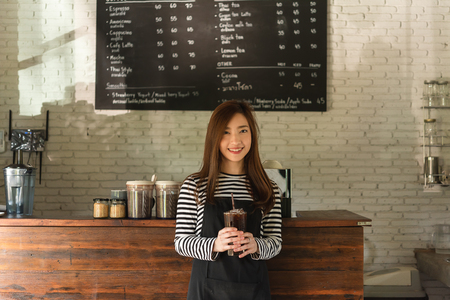 Woman coffee shop owner serving ice americano, young entrepreneur